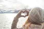 Young woman makes a heart shape finger frame on lake mountain landscape.
