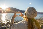 istock Woman framing beautiful landscape into heart shape 627196374