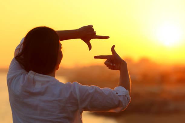 夕暮れ時の指とフレーミングの女性 ストックフォト