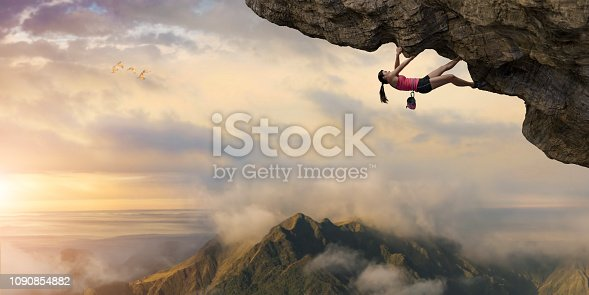 A woman free climber climbing the underside of an overhang of rock, high above a mountain peak. The free climber is wearing a sports vest and shorts, climbing shoes and is wearing a chalk bag, and is climbing as an extreme sport without safety equipment under a beautiful dawn sky.