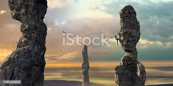 A young woman wearing leggings, top, climbing shoes with chalk bag hanging from a rock face with one arm and foothold, reaches down to her chalk bag. The rock climber is free climbing a tall eroded column rock formation, climbing high up, close to other rock columns under a beautiful dawn sky.