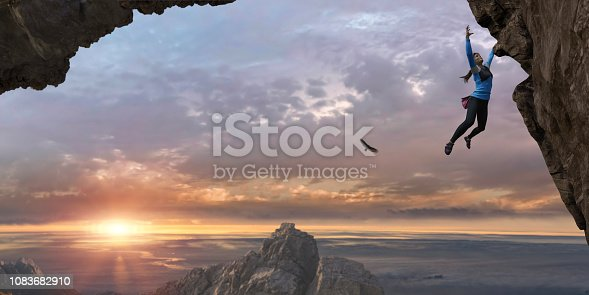 A young woman wearing climbing leggings, top, climbing shoes with chalk bag hanging from a rock face with one arm and reaching for a hold with the other. The rock climber is ascending a sheer rock face, climbing high up, close to other mountain peaks under a beautiful dawn sky.