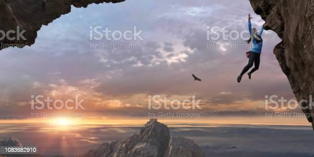 Photo of Woman Free Climbing Sheer Rock Face High Up At Sunrise