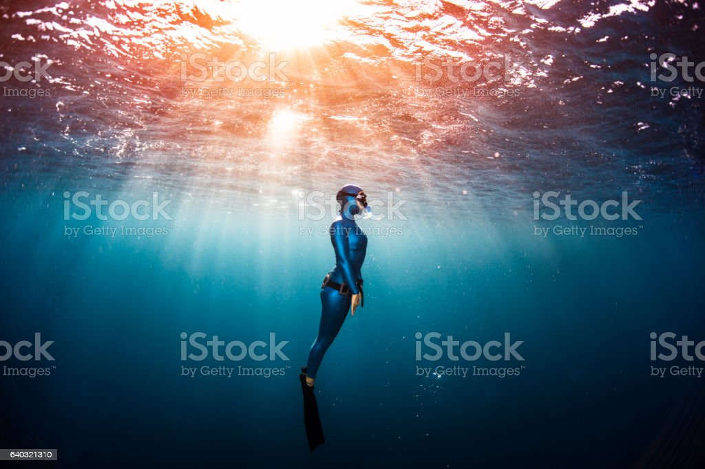 Woman free diver ascending from the depth stock photo