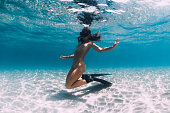 Woman free diver with fins posing over sandy sea. Freediving underwater in blue ocean