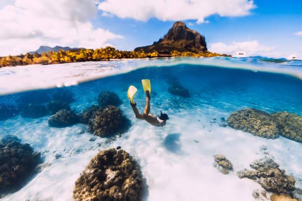 Frau Freediver gleitet über sandiges Meer mit gelben Flossen in transparentem Ozean. Freitauchen in Mauritius – Foto