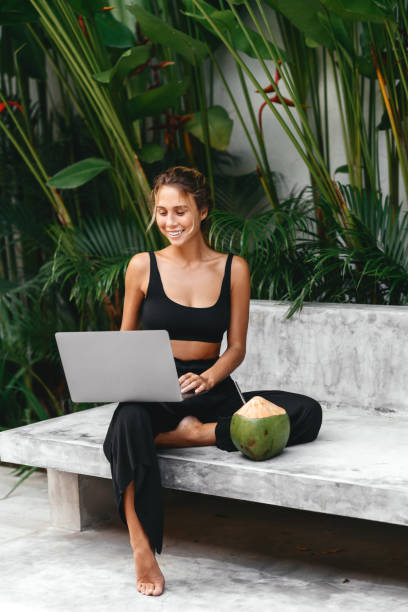 woman freelance work typing on laptop with fresh coconut . - mulher natureza flores e piscina imagens e fotografias de stock