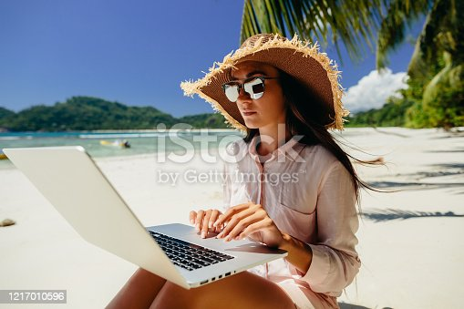 Woman freelancer on the beach. Working remotely on the laptop computer through the internet. Working while travelling. Summer vacation in Seychelles.