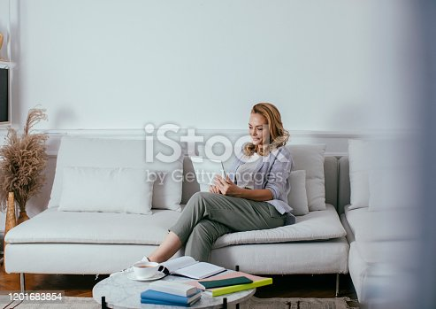 Beautiful blonde Caucasian woman sitting at living room and using her tablet.