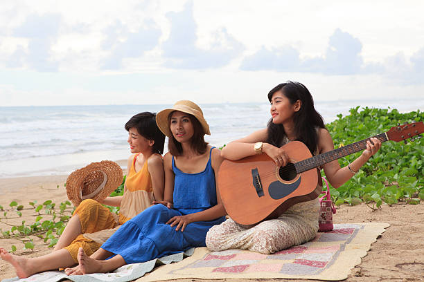 woman friend playing guitar on sea beach stock photo