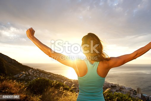 istock Woman from behind stretching out arms by sunrise 539331382