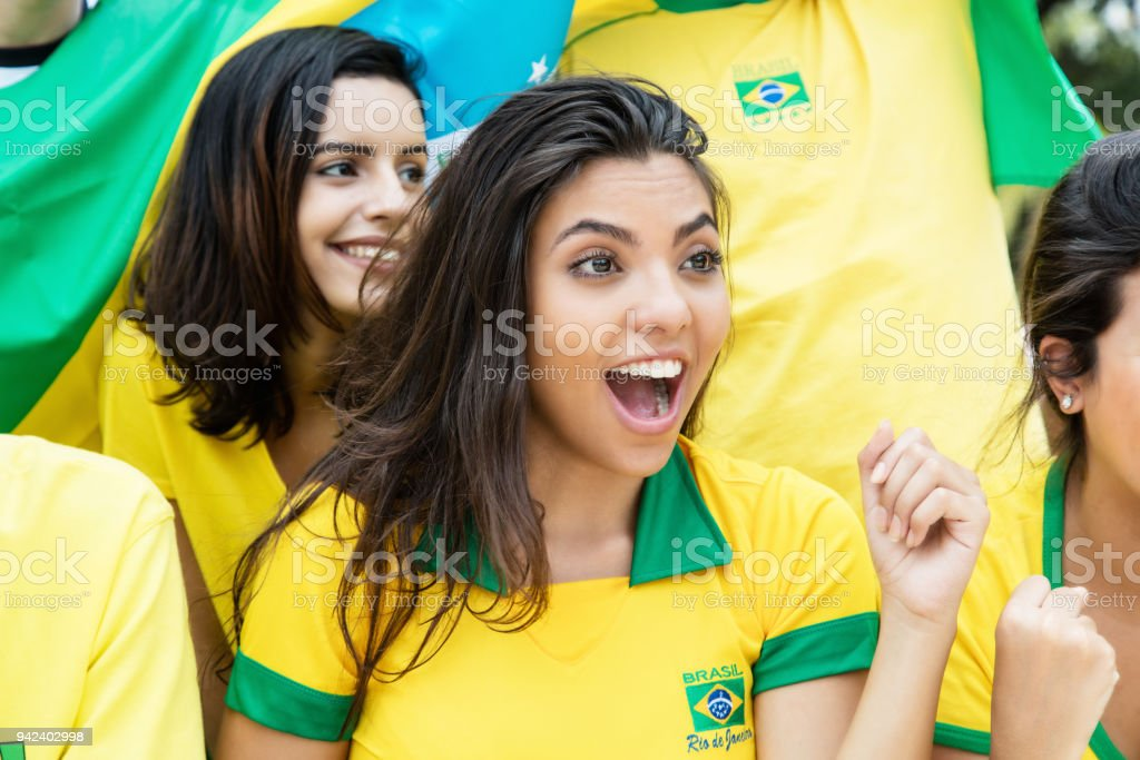 woman from brazil with other brazilian soccer fans at stadium stock