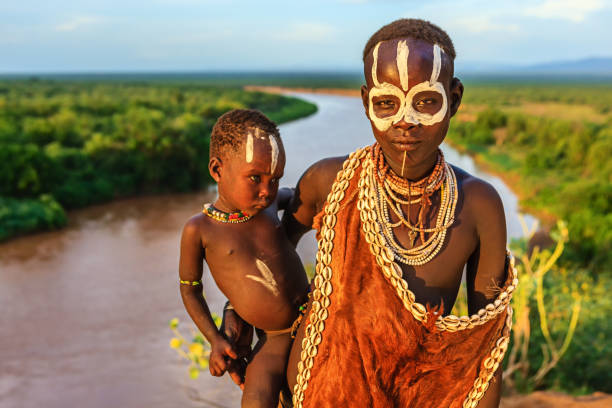 woman from karo tribe holding her baby, ethiopia, africa - horn of africa stock photos and pictures