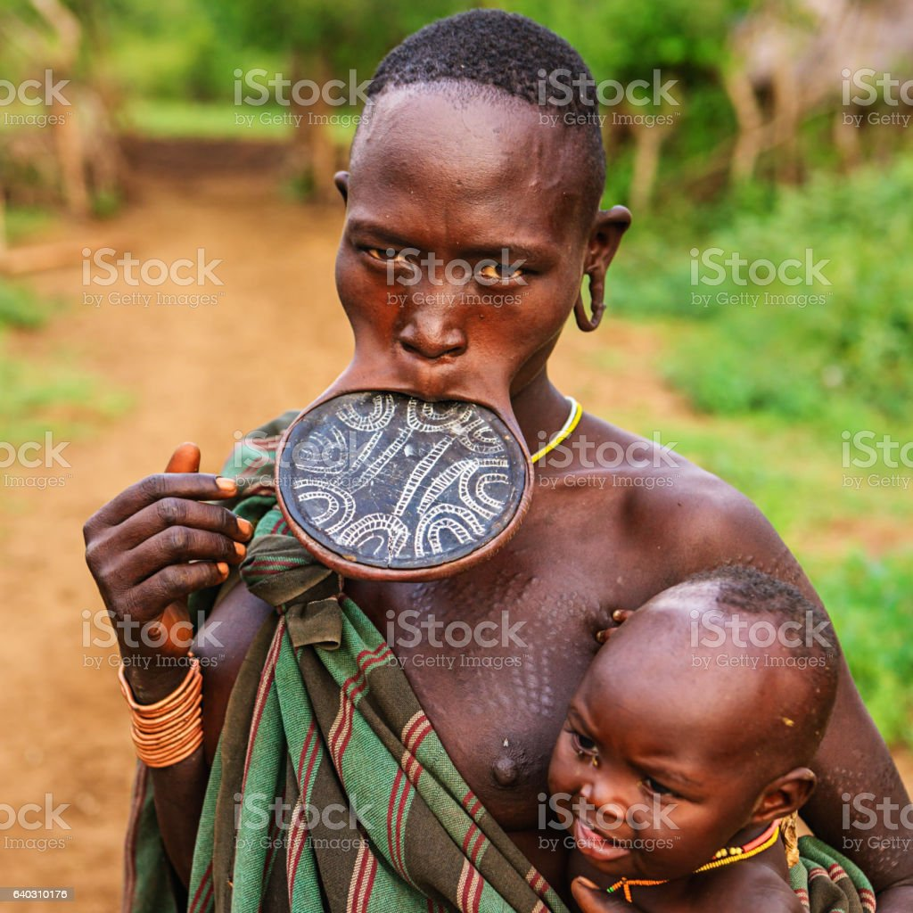 Woman from Mursi tribe breasfeeding her baby, Ethiopia, Africa stock photo