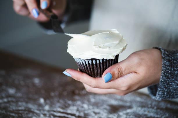 frau einen cupcake frosting - cupcake, zuckerguss stock-fotos und bilder