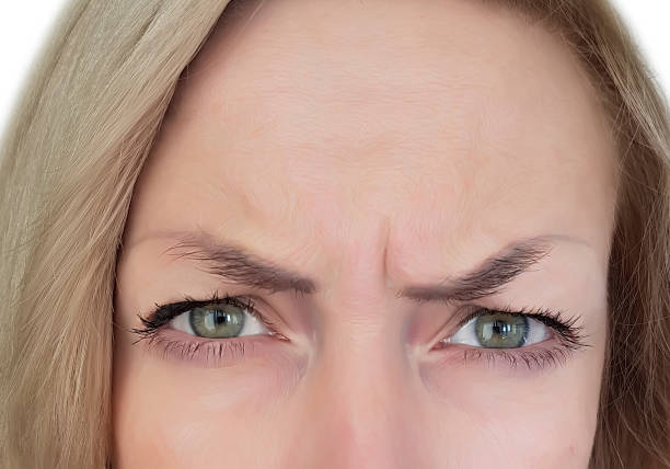 woman frowns forehead - frowning stock photos and pictures