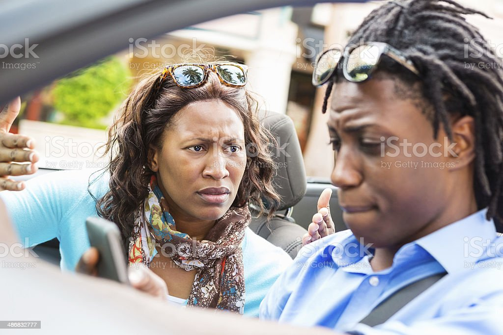 Woman frustrated with her driver using cell phone stock photo