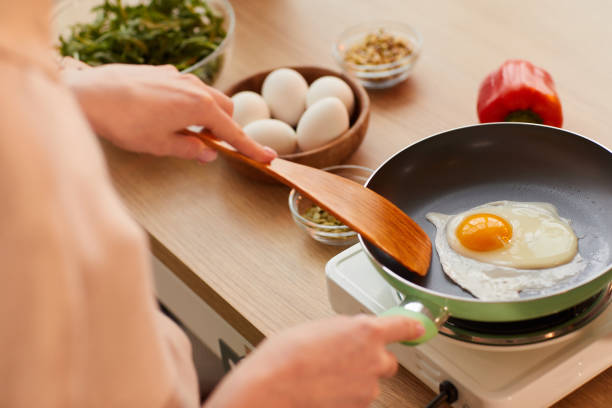 Woman Frying Eggs for Breakfast stock photo