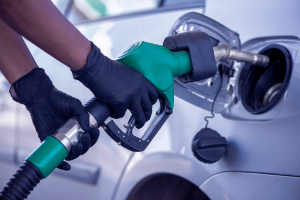 A woman fuelling gasoline at a gas station during coronavirus. stock photo