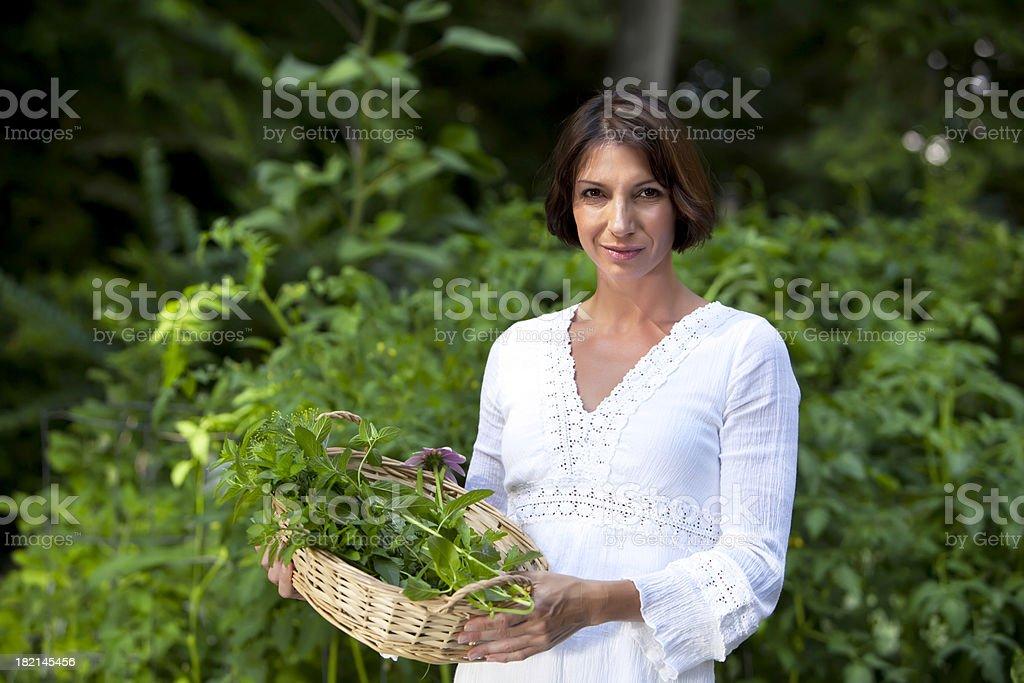 Woman gardener holding basket of herbs royalty-free stock photo