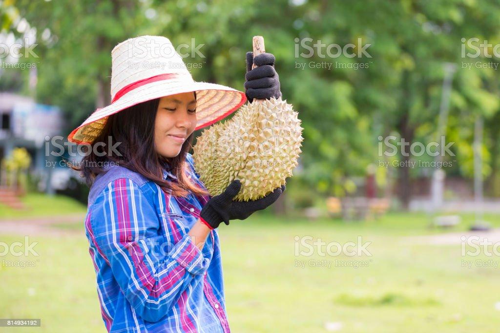 woman gardener holding durian stock photo