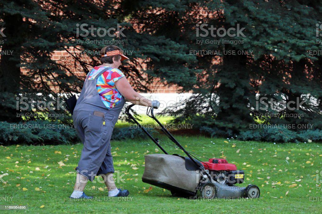 Woman mowing green grass stock image. Image of garden