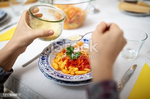Close-up of a woman adding grated cheese to the pasta while sitting at dining table. Woman garnishing pasta with grated cheese.