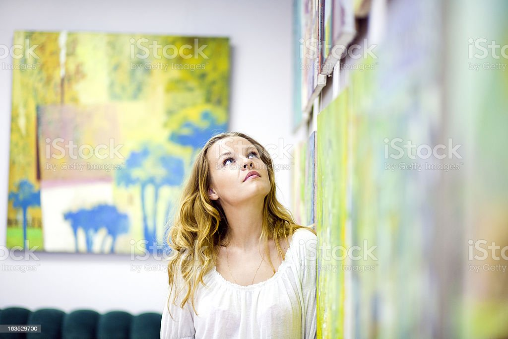 Woman gazing at artwork on the wall stock photo