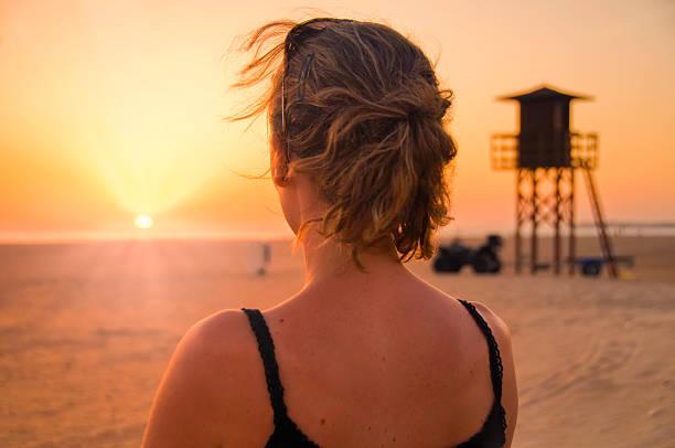 Femme en admirant le coucher du soleil - Photo