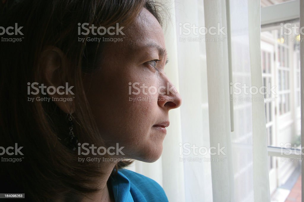 Woman gazing pensively out a window royalty-free stock photo