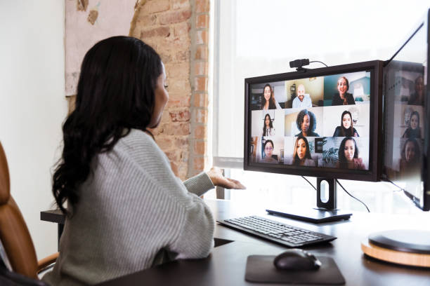 Woman gestures while brainstorming with co-workers via video conference stock photo