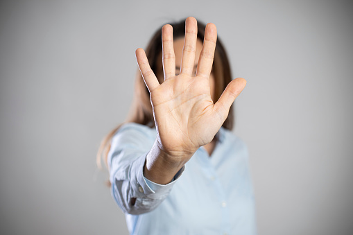 Young woman showing gesture stop. Violence against women concept