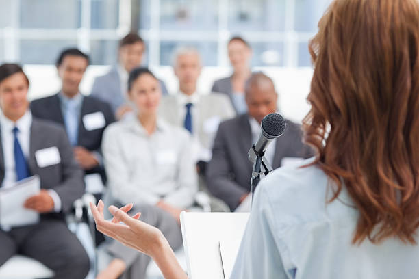 Woman gesturing while making a speech to business team stock photo