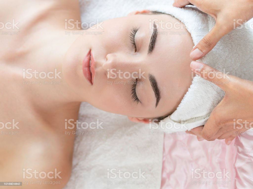 Woman gets facial and head massage in luxury spa. stock photo