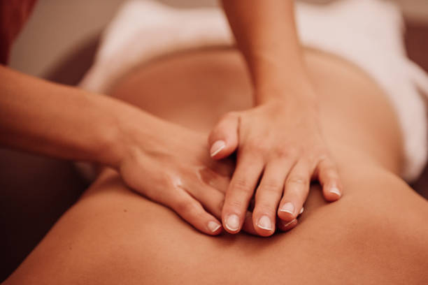 woman getting a back massage woman getting a back massage at a spa  Photo taken indoors with stobe light massaging stock pictures, royalty-free photos & images