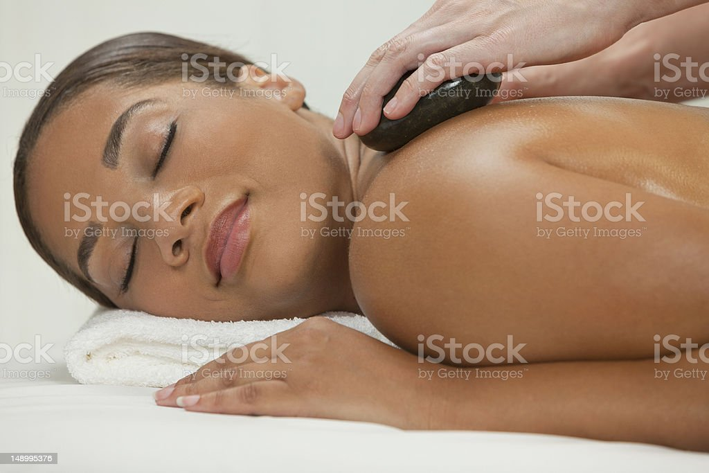 A woman getting a hot stone massage at a spa royalty-free stock photo