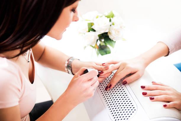 frau sich eine maniküre - nailstudio stock-fotos und bilder