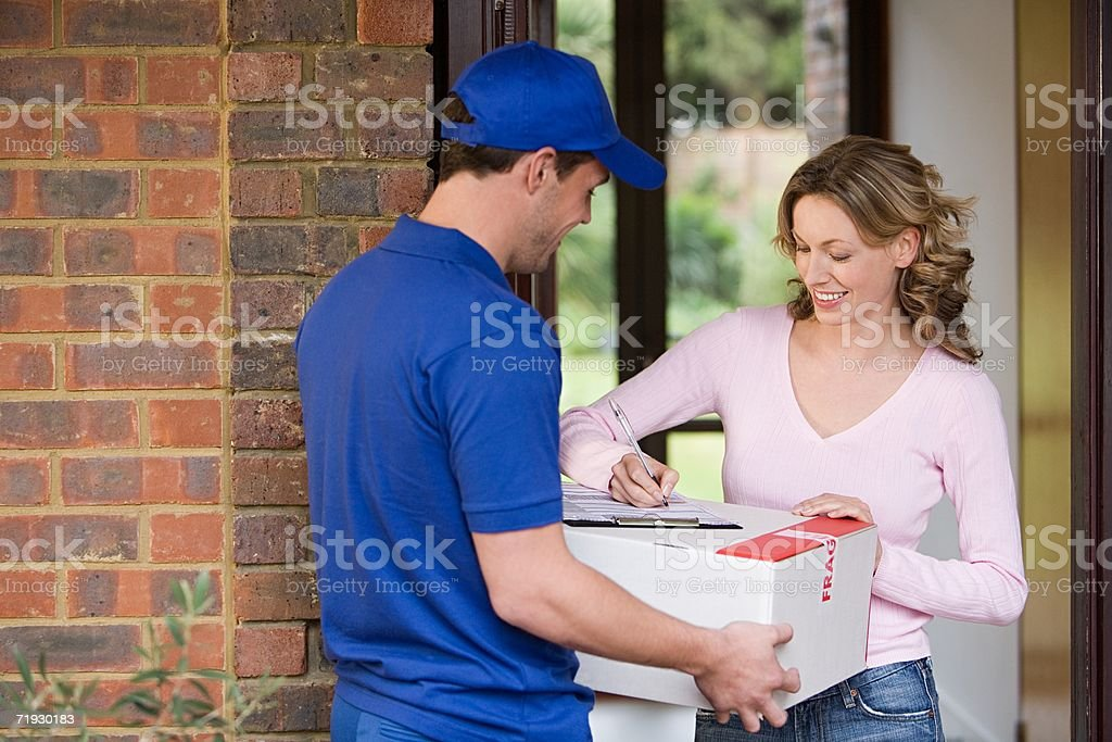 Woman getting a parcel from delivery man royalty-free stock photo
