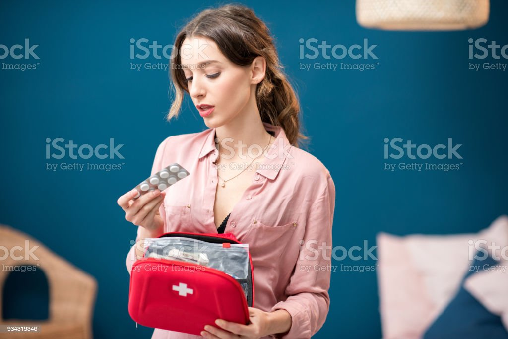 Woman getting a pills from first aid kit standing indoors in the blue...