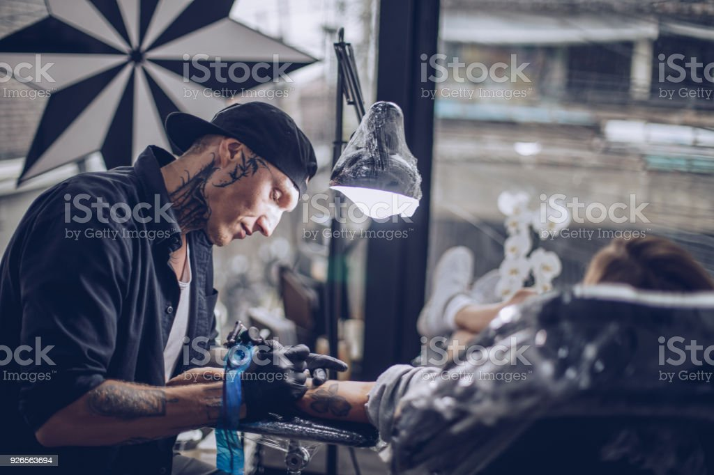 Woman getting arm tattoo stock photo