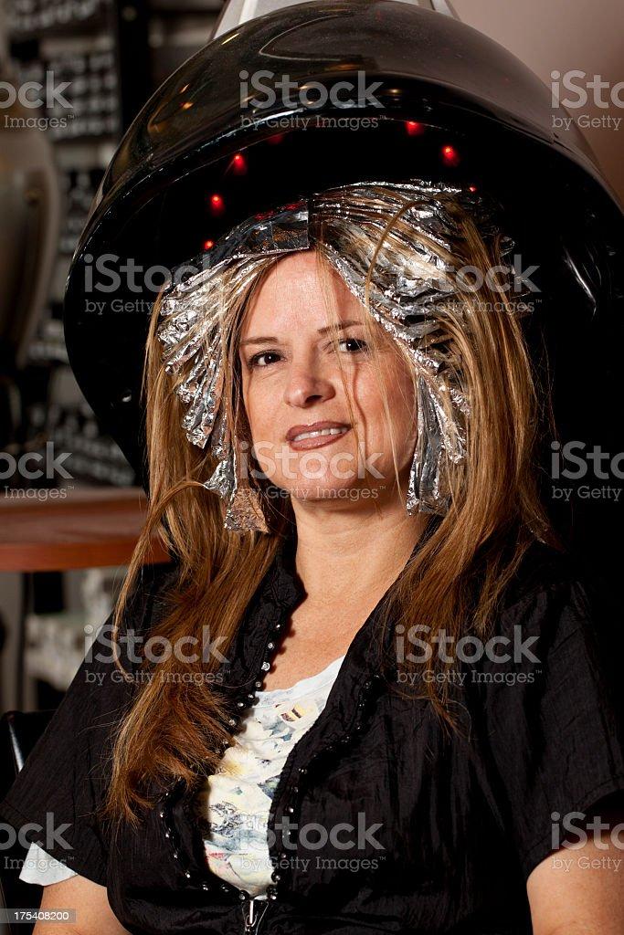 Woman Getting Blond Hair Highlights Under Hair Dryer Stock Photo