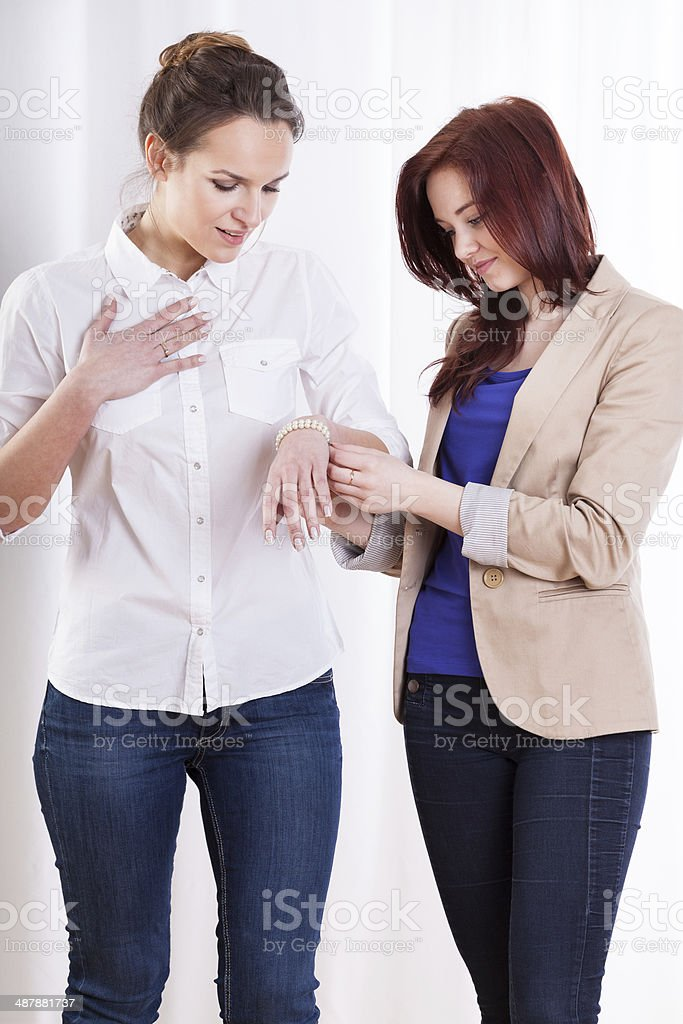 Woman getting bracelet from friend royalty-free stock photo