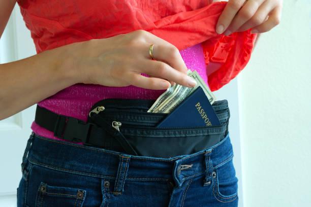 Woman getting cash and passport from hidden travel money belt stock photo