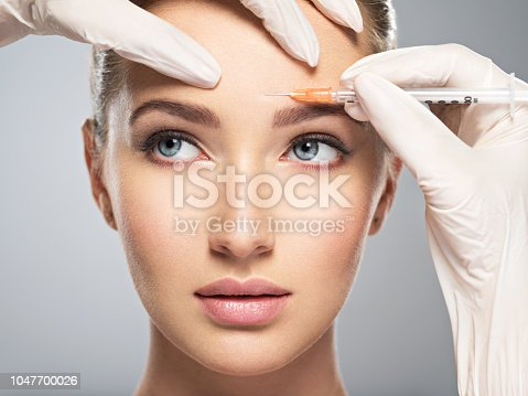 istock woman getting cosmetic botox injection in forehead 1047700026