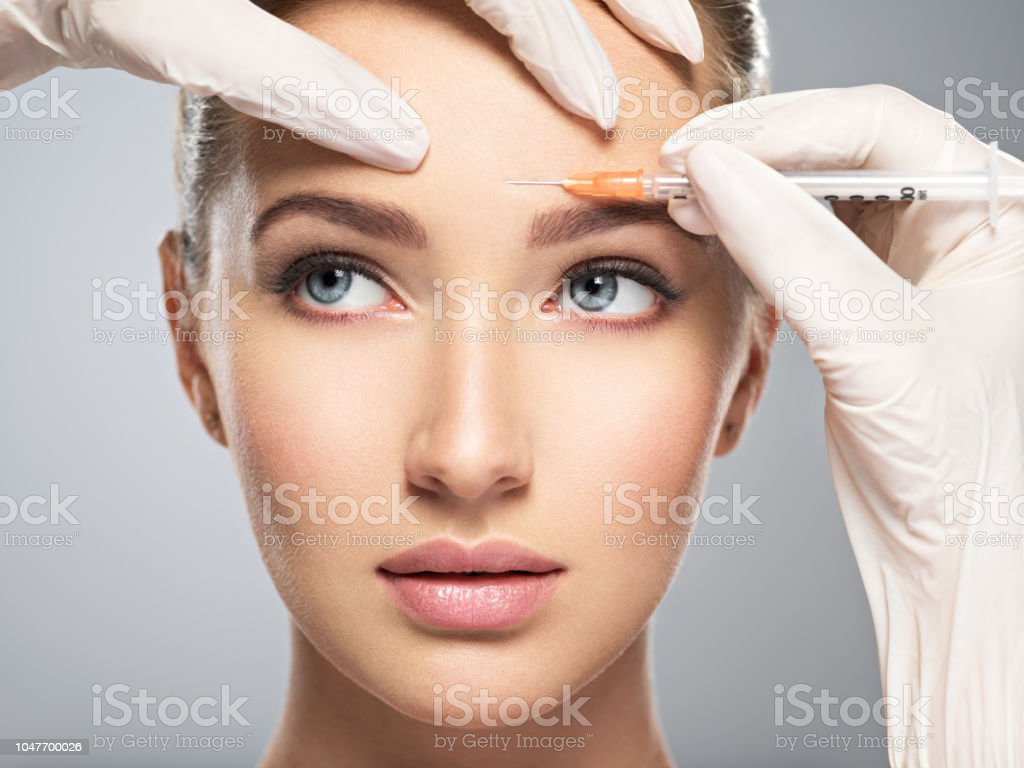 woman getting cosmetic botox injection in forehead stock photo
