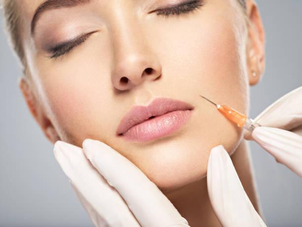 Frau bekommen kosmetische Injektion von Botox in der Backe – Foto
