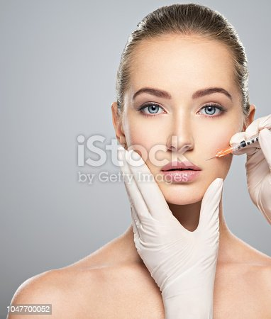 istock Woman getting cosmetic injection of botox near lips 1047700052