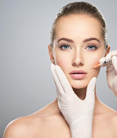 istock Woman getting cosmetic injection of botox near lips 1047700052