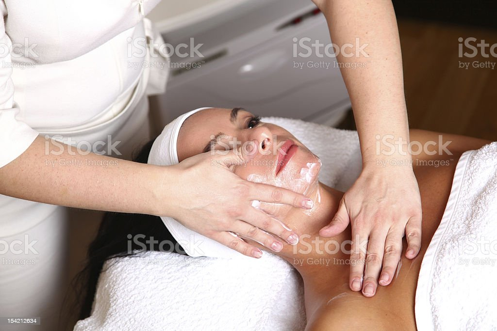 woman getting cream spa lotion on face for beauty treatment royalty-free stock photo