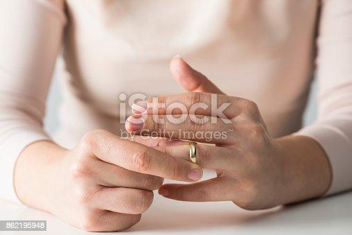 Woman taking off wedding ring.